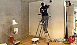 un ouvrier place une sous-couche d'accroche micro-granitée sur le mur avant de placer le stuc de terre
